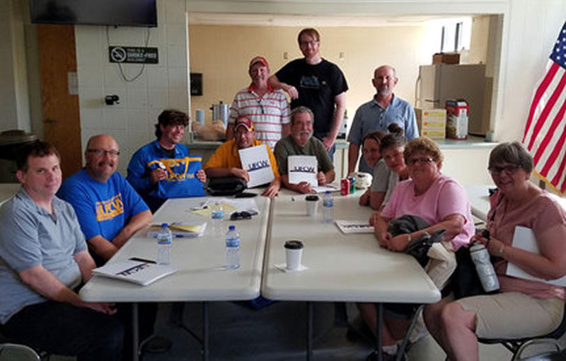 """Members of the Local 1189 bargaining committee celebrated their tentative deal with northern grocers – negotiated in a dimly lit basement at the Labor Temple after storms knocked out power in the Duluth area. """"Unable to print or make copies of the new offer, the groups met and documented the improvements the old fashioned way – in writing,"""" the union said. Photo courtesy of UFCW Local 1189."""