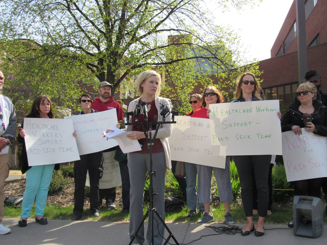Flanked by nurses and healthcare workers, Chelsie Glaubitz Gabiou, president of the Minneapolis Regional Labor Federation, recounted her work as a member of the Workplace Partnership Group. Photo by Steve Share, Minneapolis Labor Review